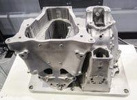 Kaksi SLM Solutions 500HL 3D-metallitulostimella tulostettua alumiinista vaihdelaatikon suojakoteloa. Kyseisen koneen kasvatusalue on 500x280x365 mm ja siinä neljä (4x400w tai 4x700w) kuitulaseria sulattavat materiaalia lujiksi tuotteiksi.