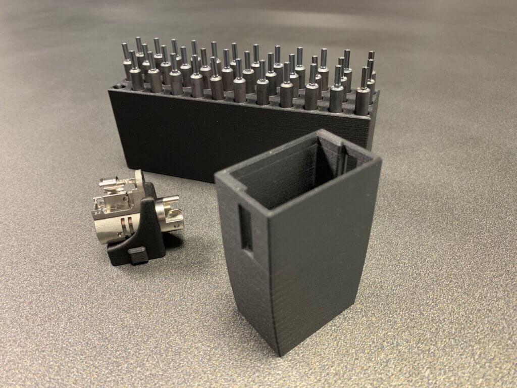 Kuvassa koneistetun tuotteen mittalaitejigi, lasermerkkauksen paikoitusjigi sekä työkaluteline.