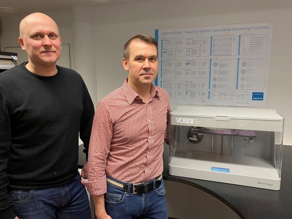 Menetelmäsuunnittelija Teppo Vendelin ja Quality Assurance Specialist Anssi Linden Markforged Mark Two 3D-komposiittitulostimen rinnalla.