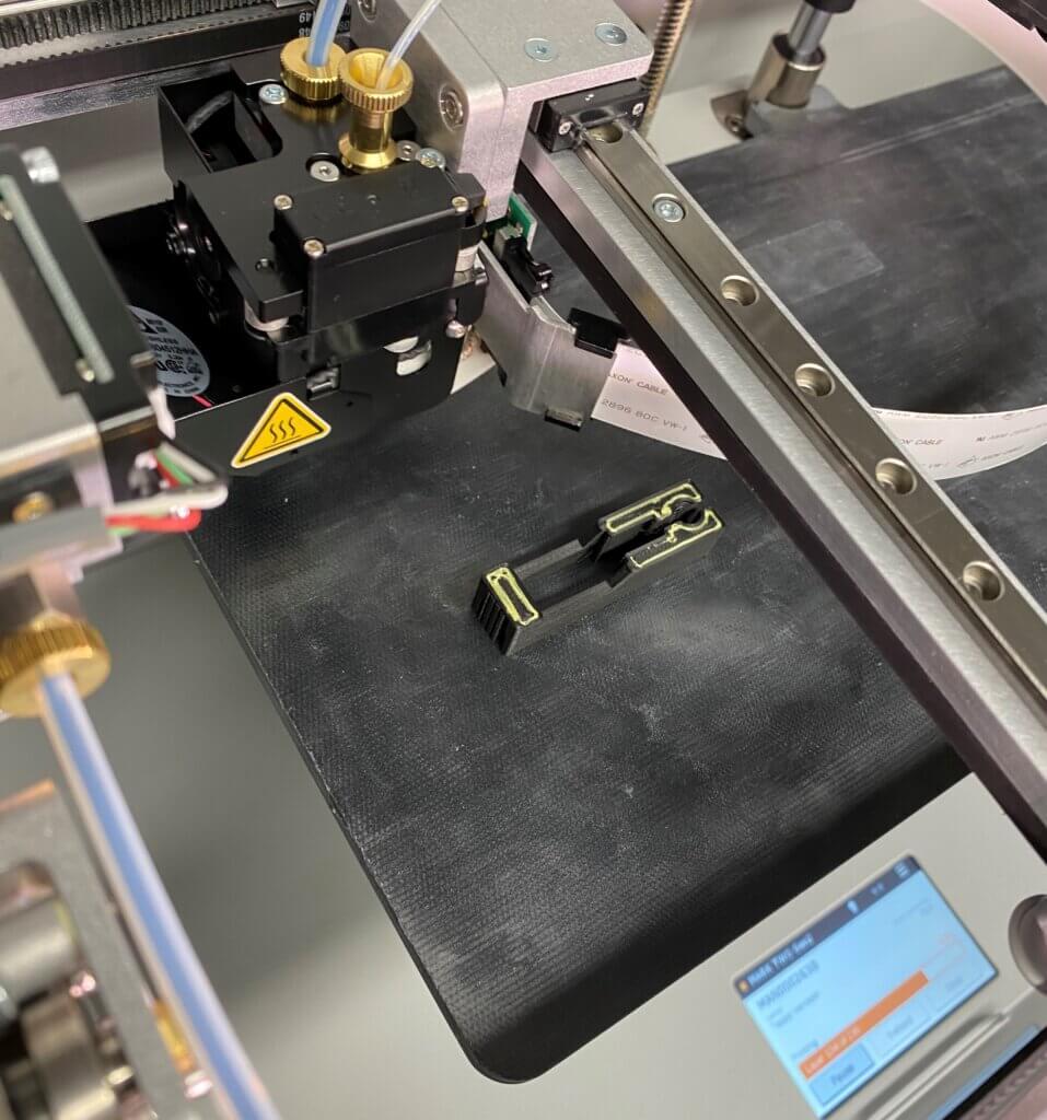 Markforged Mark Two 3D-komposiittitulostimen sidosmateriaaleina ovat Onyx (pilkottu hiilikuitu ja nylon) tai puhdas nylon sekä pitkänä kuituna (näkyy kuvassa keltaisena) hiilikuitu, kevlar, lämmönkestävä lasikuitu tai normaali lasikuitu.