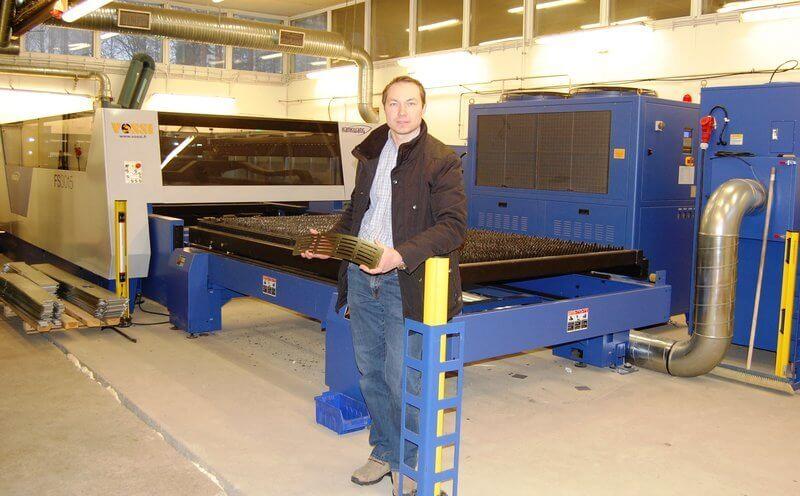 Riitek Oy:n toimitusjohtaja Toni Pesonen pitää kädessään jo elektrolyysikiillotettua veneen kansiritilää, mikä on leikattu uudella Vossin toimittamalla Hankwang FS3015 4 kW levylaserilla.