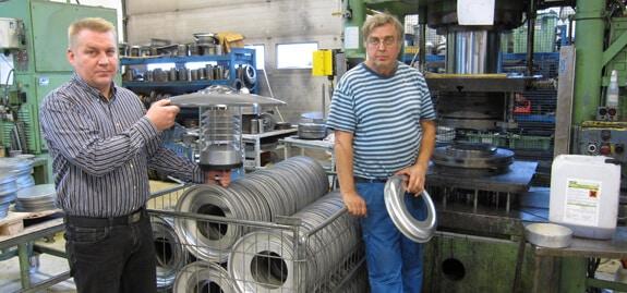 """Yli 40 vuotta syvävetotöitä tehnyt Lars Saarikangas (oik.) kehuu Irmcon tarjoamia muovausominaisuuksia sekä kappaleiden puhtautta. """"Työympäristömme on nyt siistimpi, kun työkappaleista ei valu öljyä ja myös luonto säästyy. Olemmekin päättäneet, että siirrymme kaikessa valmistuksessa käyttämään öljytöntä Irmcoa"""", toimitusjohtaja Simo Tuppuri kertoo ja pitää kädessään uutta Ohkola valaisinta."""