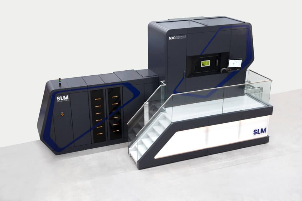 SLM Solutions NXG XII 600 on täynnä innovatiivisia teknisiä ominaisuuksia, kuten lasersäteen zoomaus-toiminto korkeimman tuottavuuden ja luotettavuuden saavuttamiseksi. Uutuudessa on myös useita automatisoituja ominaisuuksia, kuten automaattinen kasvatussylinterinvaihto, automaattinen kasvatuksen käynnistys sekä kasvatussylinterin ulkoinen esilämmitysasema ja ulkoinen jauheenpoistoasema.