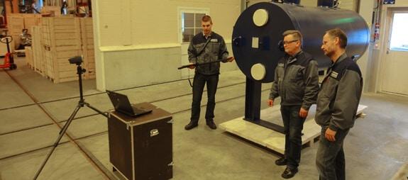 Laatuinsinööri Anssi Myllymaa (vas.) mittaa langattomalla Metronor 3D-mittalaitteella korealaisasiakkaalle toimitettavaa levylämmönsiirrintä. Toimenpidettä seuraavat teknologiajohtaja Paavo Pitkänen ja laatupäällikkö Juha Suominen.